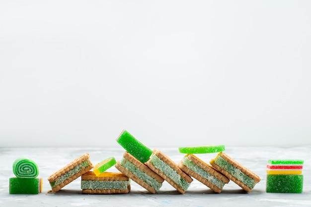 Een vooraanzicht sandwich koekjes heerlijk met marmelade op het witte koekje van het bureau