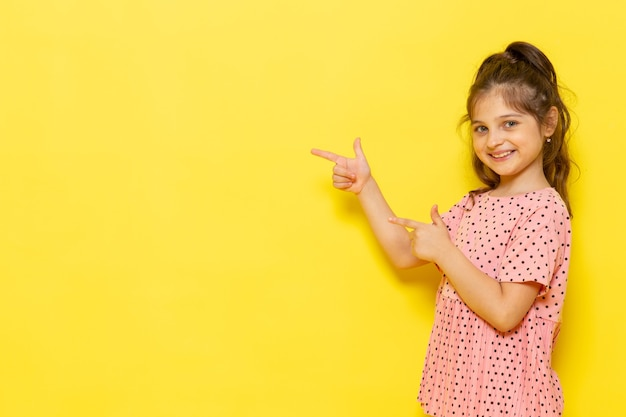 Een vooraanzicht schattig klein kind in roze jurk glimlachend en wijzen
