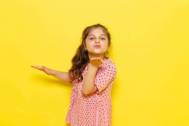 Een vooraanzicht schattig klein kind in roze jurk kus verzenden