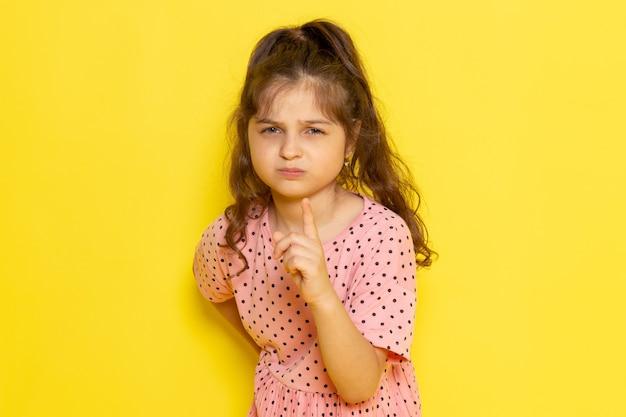 Een vooraanzicht schattig klein kind in roze jurk met dreigende uitdrukking