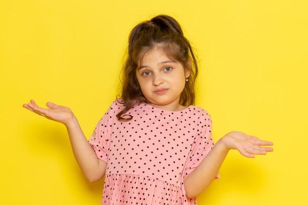 Een vooraanzicht schattig klein kind in roze jurk met een verwarde uitdrukking