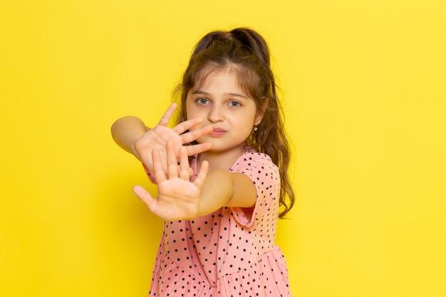 Een vooraanzicht schattig klein kind in roze jurk met een voorzichtige uitdrukking