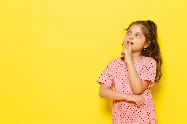 Een vooraanzicht schattig klein kind in roze jurk poseren met denken expressie