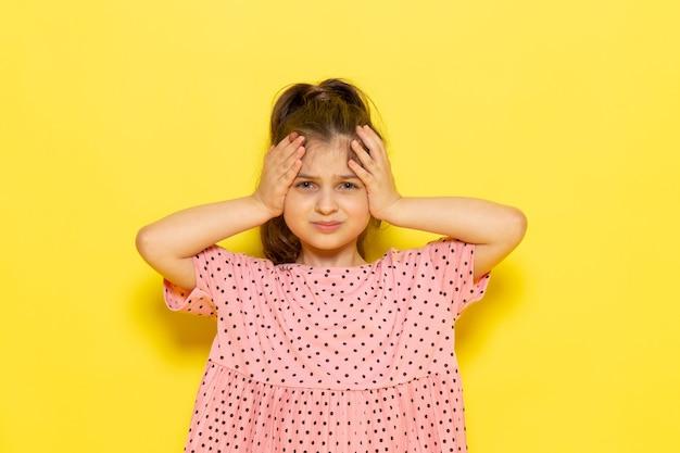 Een vooraanzicht schattig klein kind in roze jurk poseren met gestreste uitdrukking