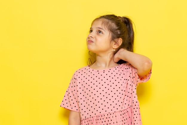 Een vooraanzicht schattig klein kind in roze jurk poseren met ontevreden uitdrukking