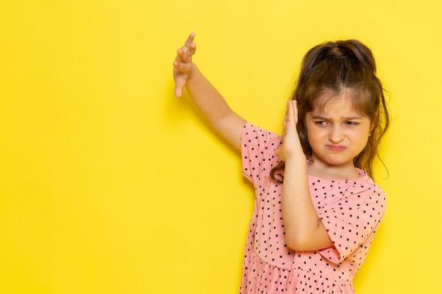 Een vooraanzicht schattig klein kind in roze jurk poseren met voorzichtige uitdrukking