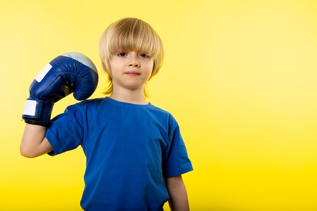 Een vooraanzicht schattige blonde jongen poseren in blauw t-shirt en blauwe handschoen op de gele muur