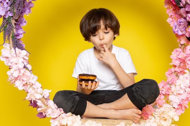 Een vooraanzicht schattige jongen donuts eten in wit t-shirt op de gele vloer