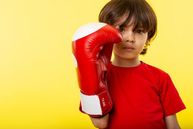 Een vooraanzicht schattige jongen in rode bokshandschoenen en rode t-shirt op de gele muur