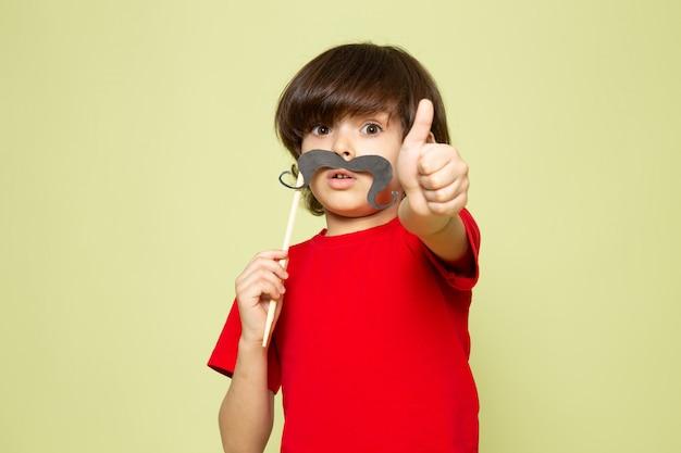 Een vooraanzicht schattige jongen in rode t-shirt met snor op de steen gekleurde ruimte