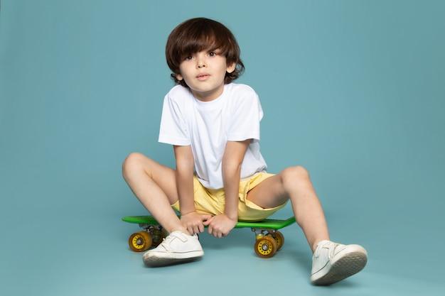 Een vooraanzicht schattige jongen in wit t-shirt en gele korte broek rijden groene skateboard op de blauwe ruimte