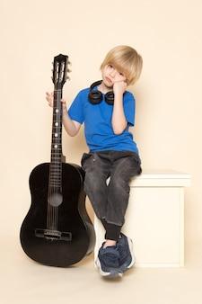 Een vooraanzicht schattige kleine jongen in blauw t-shirt met zwarte koptelefoon met zwarte gitaar