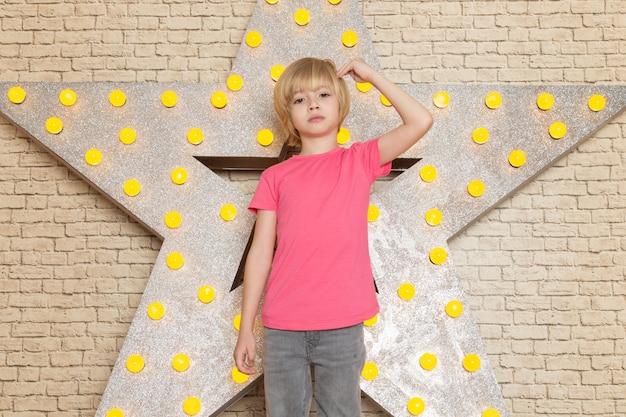 Een vooraanzicht schattige kleine jongen in roze t-shirt grijze jeans op de ster ontworpen gele standaard en lichte achtergrond
