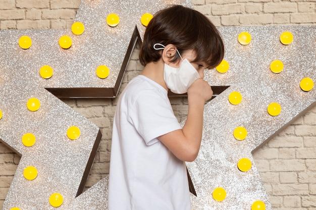 Een vooraanzicht schattige kleine jongen in wit t-shirt donkere jeans wit steriel masker op de ster ontworpen gele standaard en lichte achtergrond