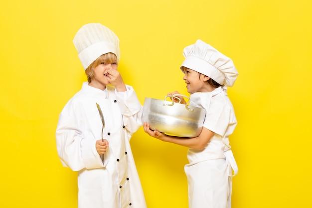 Een vooraanzicht schattige kleine kinderen in witte kokkostuums en witte kokskappen met een grote lepel en een zilveren pan glimlachend op de gele muur