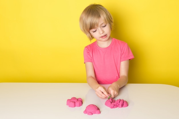 Een vooraanzicht schattige schattige jongen in roze t-shirt spelen met kleurrijke kinetisch zand