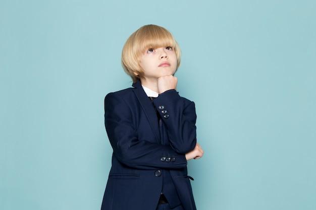 Een vooraanzicht schattige zakelijke jongen in blauwe klassieke pak poseren dagdromen denken zakelijke werk mode