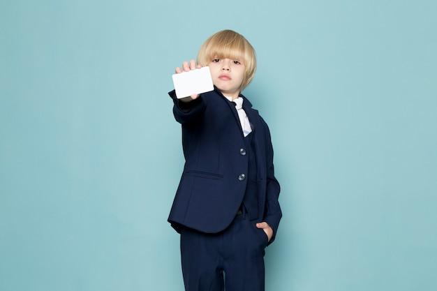 Een vooraanzicht schattige zakelijke jongen in blauwe klassieke pak poseren met witte kaart zakelijke werk mode