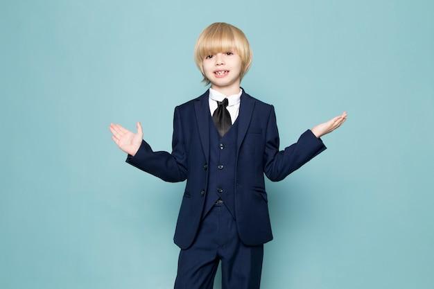 Een vooraanzicht schattige zakelijke jongen in blauwe klassieke pak poseren zakelijke werk mode