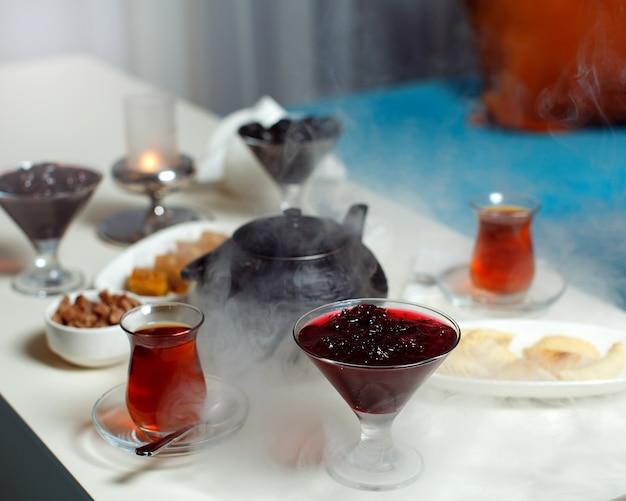 Een vooraanzicht tafel theetafel met hete thee jam en lieverds op de witte tafel