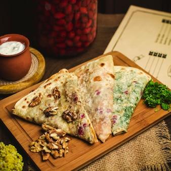 Een vooraanzicht van dichtbij qutabs met vlees groene kruiden en pompoen op het bruine bureau