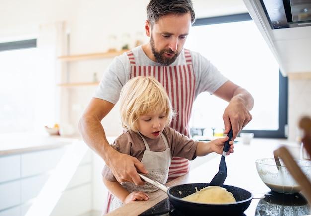 Een vooraanzicht van een kleine jongen met vader binnenshuis in de keuken die pannenkoeken maakt.