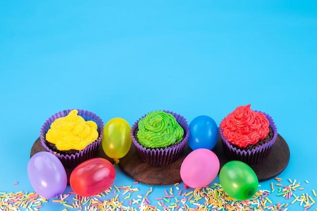 Een vooraanzicht van heerlijke brownies in paarse vormen op basis van chocolade, samen met snoepjes op blauw, snoepcake koekjeskleur