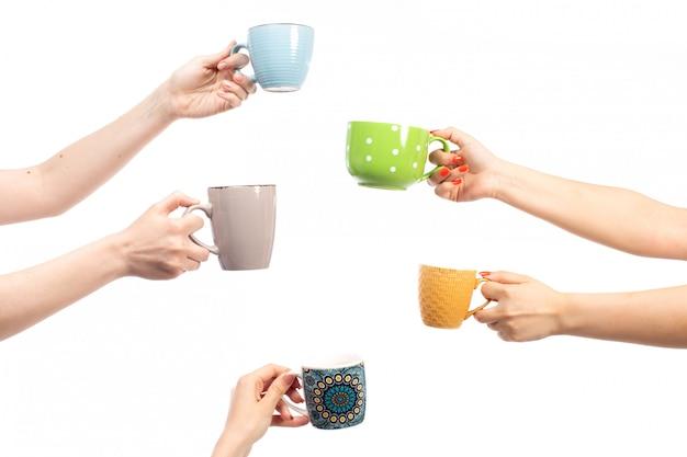 Een vooraanzicht vermenigvuldigt vrouwelijke handen die verschillende gekleurde koppen op het wit houden