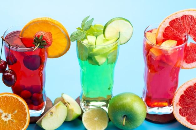 Een vooraanzicht vers fruitcocktails met vers fruitplakken ijskoeling op blauw, drink de kleur van het sapcocktailfruit