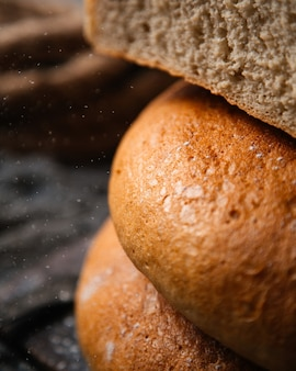 Een vooraanzicht vers gebakken brood en smakelijk het broodbroodje van het voedseldeeg