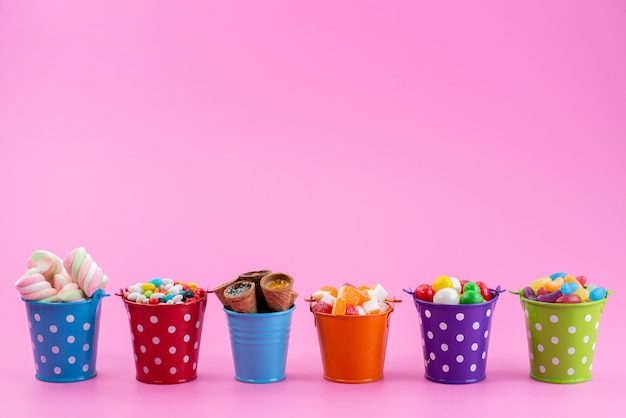 Een vooraanzicht verschillende snoepjes zoals confitures marmelades snoepjes in manden op roze, suikerzoete kleur