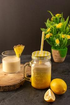 Een vooraanzicht verse cocktail lekker koel drankje binnen kan met stro dichtbij houten bureau samen met citroenen op de donkere achtergrond de zomersap drinken