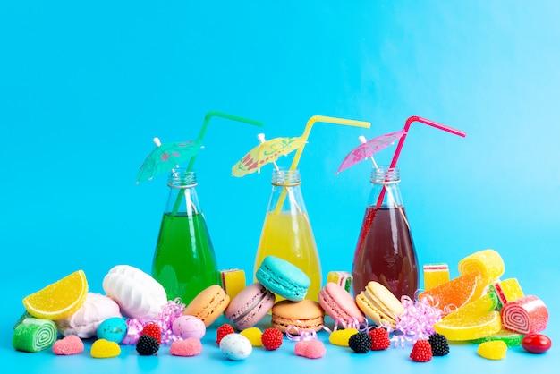 Een vooraanzicht verse cocktails gekleurd met franse macarons marmelades en marshmallow allemaal op blauw