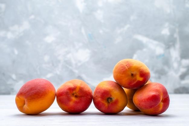 Een vooraanzicht verse perziken en zacht op de witte fruitkleur als achtergrond
