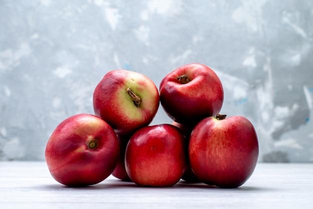 Een vooraanzicht verse perziken zuur en zacht op de witte achtergrond fruit kleur frisse zomer