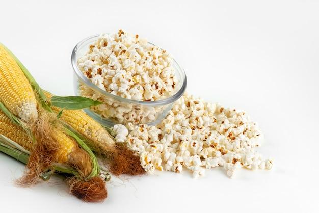 Een vooraanzicht verse popcorn met gele, rauwe likdoorns op wit, de snackzaad van de voedselmaaltijd