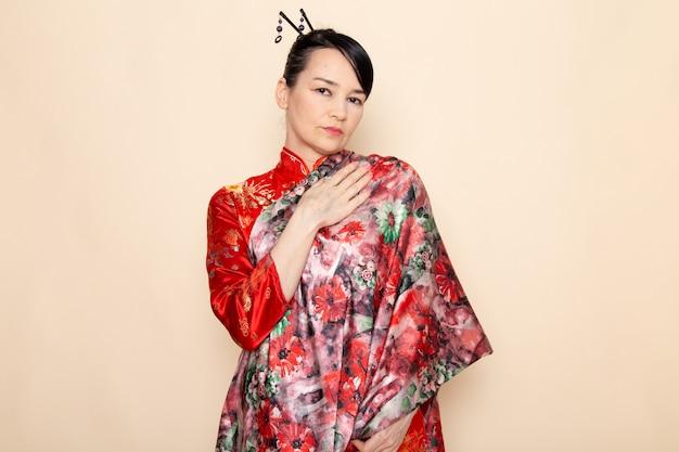 Een vooraanzicht voortreffelijke japanse geisha in het traditionele rode japanse kleding stellen met bloem ontworpen weefsel elegant op de room achtergrondceremonie japan