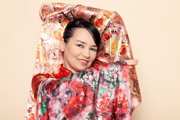 Een vooraanzicht voortreffelijke japanse geisha in het traditionele rode japanse kleding stellen met het bloem ontworpen weefsel elegante glimlachen op de room achtergrondceremonie japan