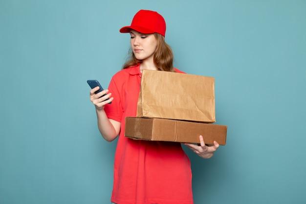 Een vooraanzicht vrouwelijke aantrekkelijke koerier die in rood poloshirt rood glb bruin pakket houden die telefoon met behulp van op de blauwe baan van de achtergrondvoedseldienst