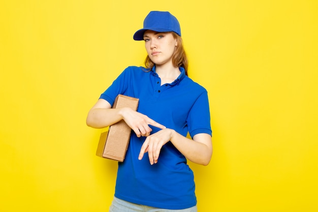 Een vooraanzicht vrouwelijke aantrekkelijke koerier in blauw poloshirt blauw glb en jeans die pakket houden wat betreft haar pols op de gele achtergrondvoedseldienst