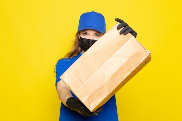 Een vooraanzicht vrouwelijke aantrekkelijke koerier in blauw poloshirt blauwe pet en jeans met pakket in zwarte handschoenen zwart beschermend masker op de gele achtergrond food service baan