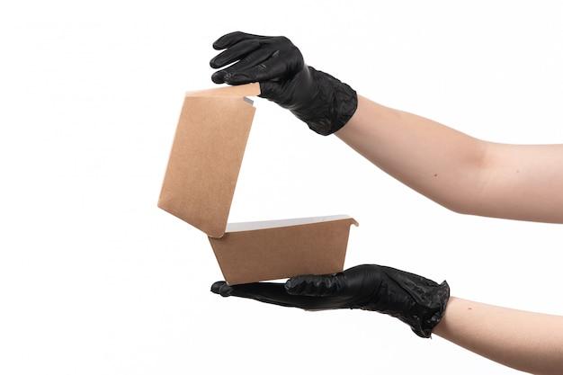 Een vooraanzicht vrouwelijke hand die een leeg voedselpakket op wit houdt