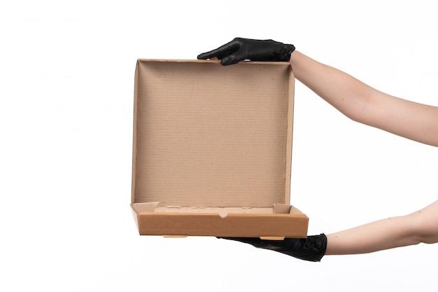 Een vooraanzicht vrouwelijke hand die een lege leveringsdoos op wit houdt