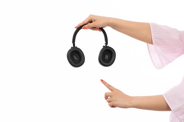 Een vooraanzicht vrouwelijke hand die zwarte oortelefoons op het wit houdt