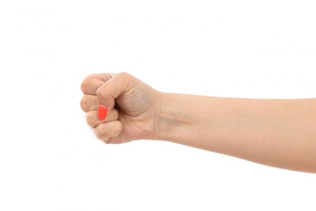 Een vooraanzicht vrouwelijke hand met gekleurde nagels strakke vuist op de witte