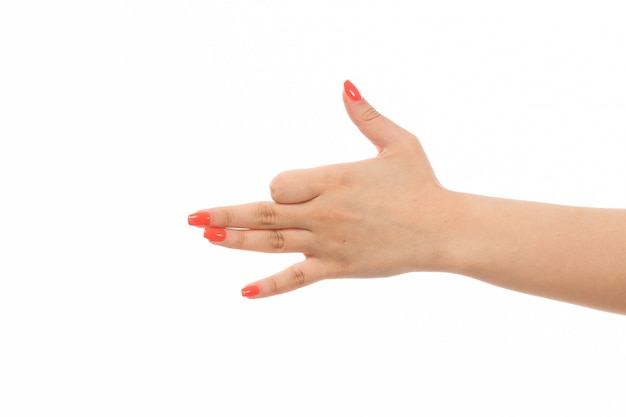 Een vooraanzicht vrouwelijke hand met gekleurde spijkers die teken op het wit tonen