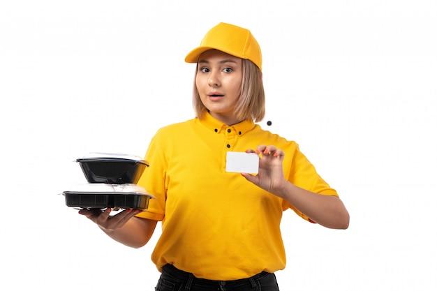Een vooraanzicht vrouwelijke koerier die in geel overhemd geel glb witte kaart en kommen met voedsel op wit houdt
