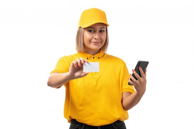Een vooraanzicht vrouwelijke koerier die in geel overhemd geel glb witte kaart en smartphone op wit houdt