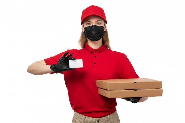 Een vooraanzicht vrouwelijke koerier die witte kaart en pizzadozen in de rode zwarte handschoenen en het masker van overhemds rode glb en wit houdt