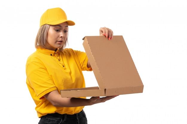 Een vooraanzicht vrouwelijke koerier in de gele die doos van de de holdingspizza van het glb gele overhemd op wit wordt verrast